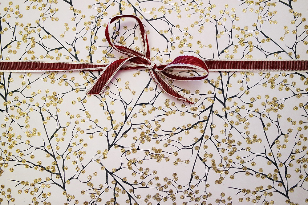 Black and gold branches on white wrapping paper with red ribbon edged in white.