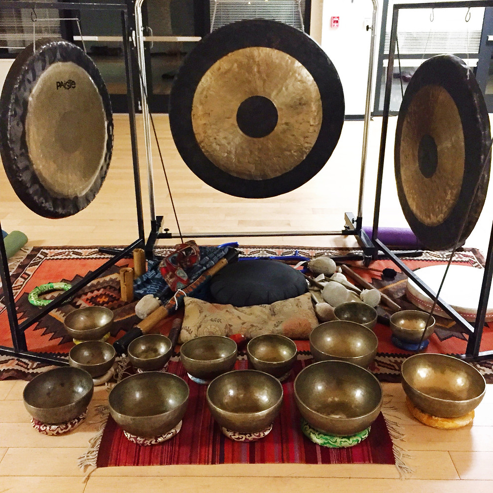 Three gongs hanging from square metal stands set around an orange patterned rug with 13 metal singing bowls of various sizes. The instruments for a sound bath set in the middle of a room with a light wood floor.