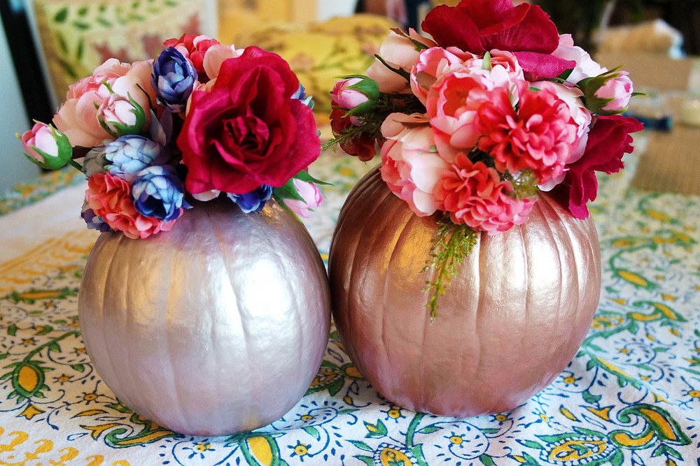 Two painted pumpkins, one copper and one silver purple, with flowers on top.