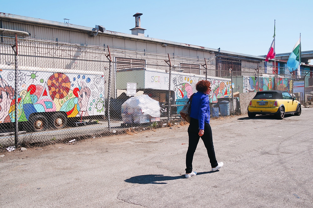 Woman with red curly hair in a bright blue jacket, black jeans, and white sneakers walking in front of a chain link fence outside of SCRAP in San Francisco