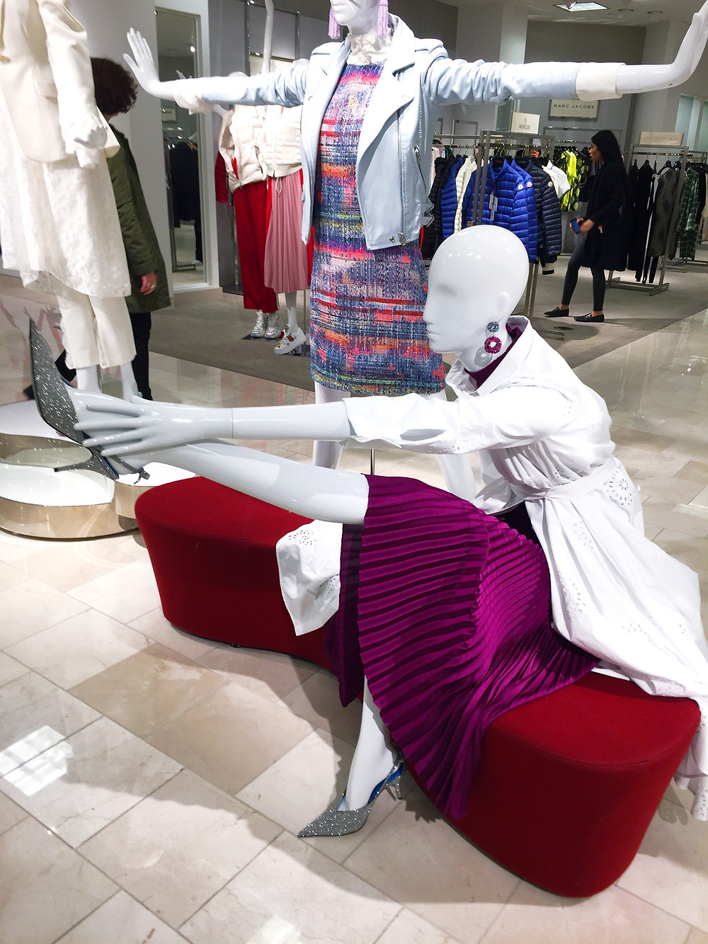 A white mannequin in a department store wearing a purple pleated skirt, white long coat and silver kitten heel slingback shoes. The mannequin is seated on a red curved bench, with one leg sticking out, reaching for that foot. Behind it stands another mannequin, wearing a rainbow colored mini dress and a silver moto jacket, with its arms and hands held straight out to the sides.