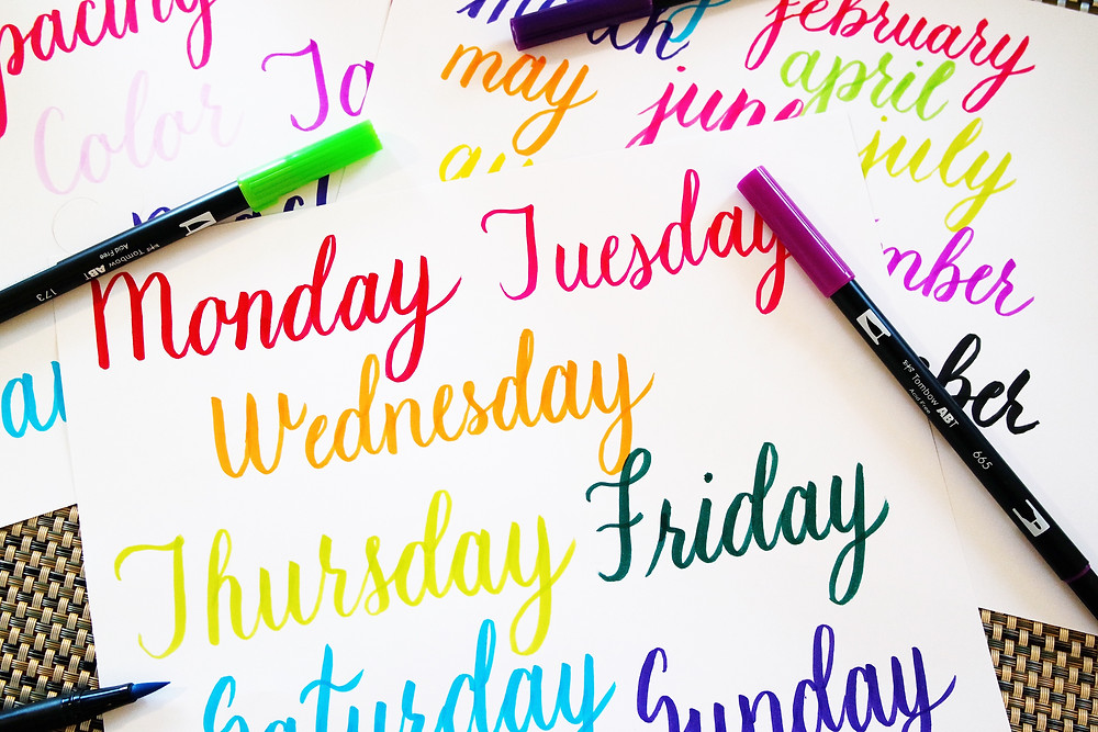 Three sheets of paper with colorful words, in colors ranging in a rainbow from red to purple, on them in lettered script lying overlapping on a textured mat with colored brush pens scattered around. The top sheet has the seven days of the week written on it.