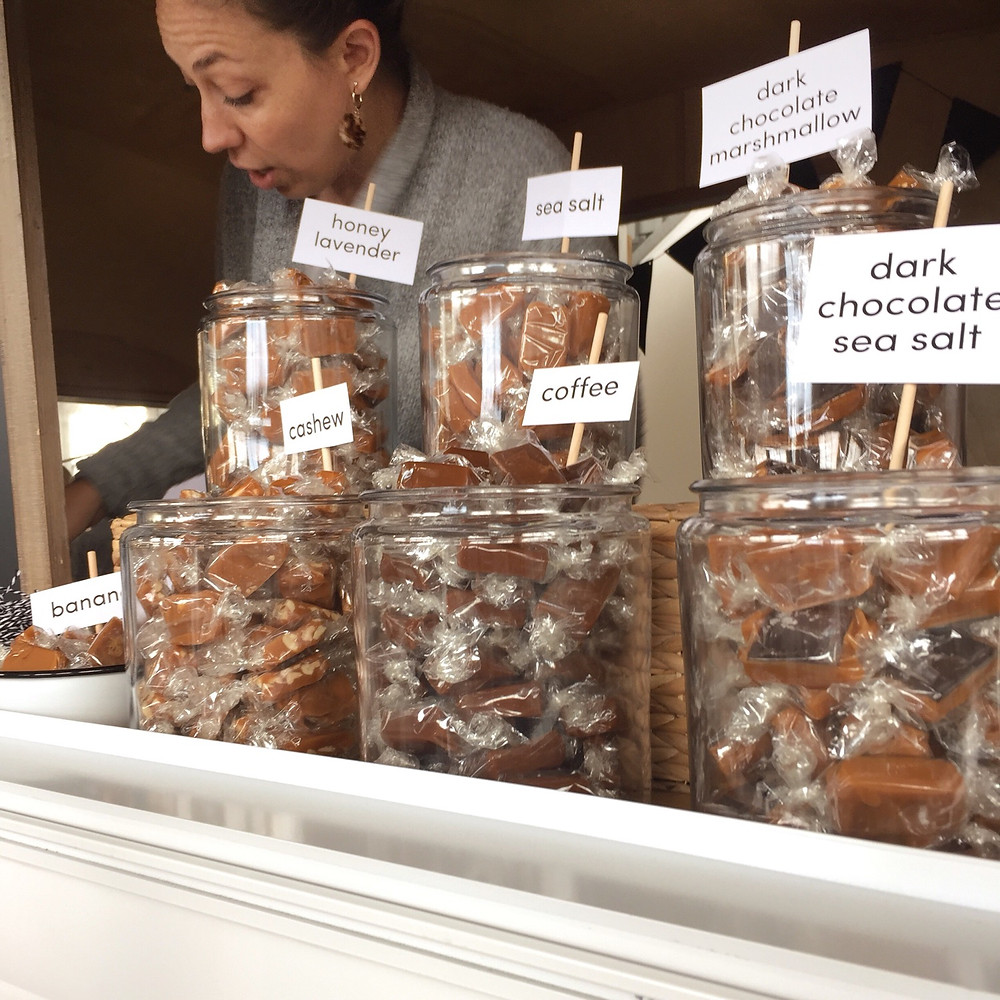 Two rows of glass jars filling with caramels. White signs on wooden dowel stick out of each jar indicating the flavor. A woman packs caramels into a wax bag.