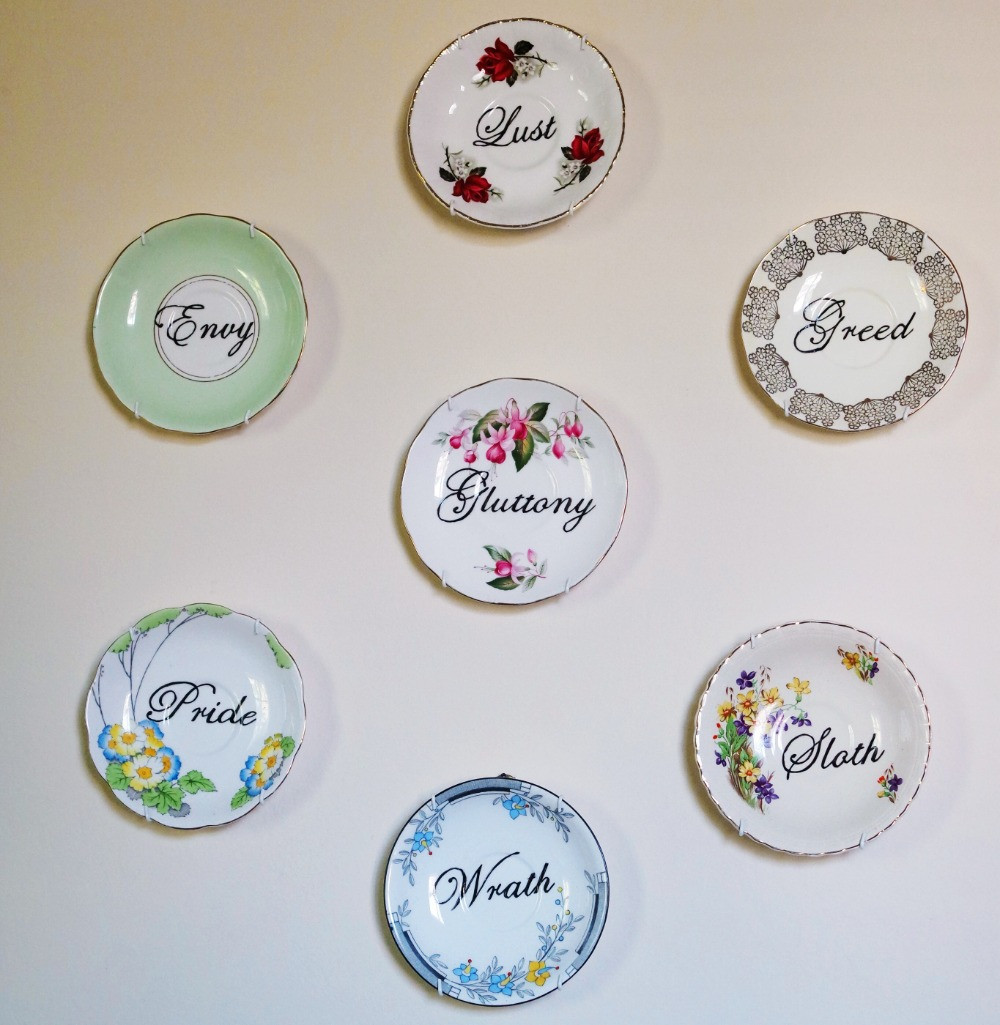 Seven saucers on a wall, each one with one of the seven deadly sins written on it in cursive.