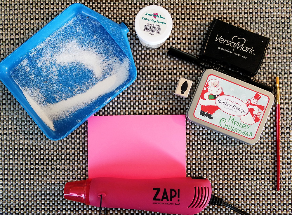 Heat embossing supplies - small blue tray with white embossing powder, jar of white embossing powder, versamark stamp pad and pen, small paintbrush, hot pink card, zap heat gun, and rubber stamps.