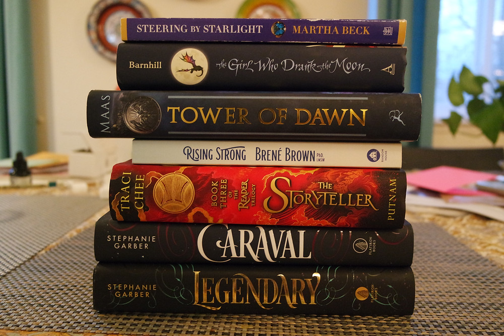 Stack of books on a table - Steering by Starlight, The Girl Who Drank the Moon, Tower of Dawn, Rising Strong, The Storyteller, Caraval, and Legendary.