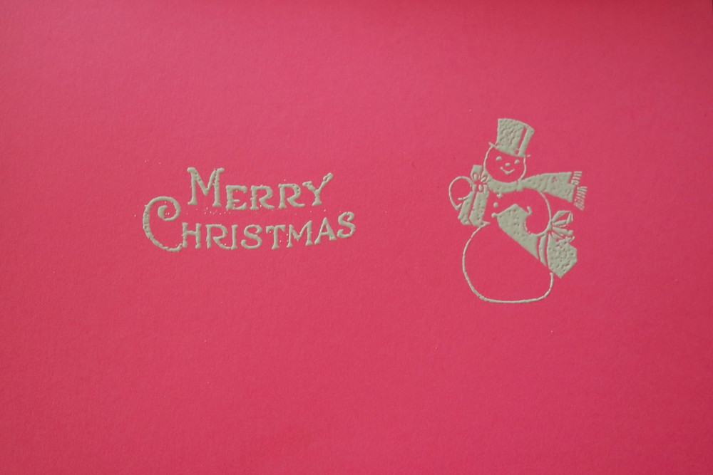 """Hot pink card showing a snow man wearing a top hat and scarf, carrying presents, in white, with the phrase """"Merry Christmas"""" also in white."""