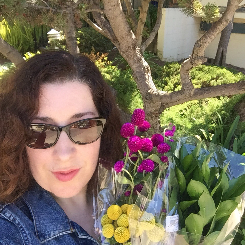 Sophia Dunkin-Hubby wearing sunglasses, holding bunches of grocery store flowers, purple, greenery, and yellow, standing in front of trees and bushes.
