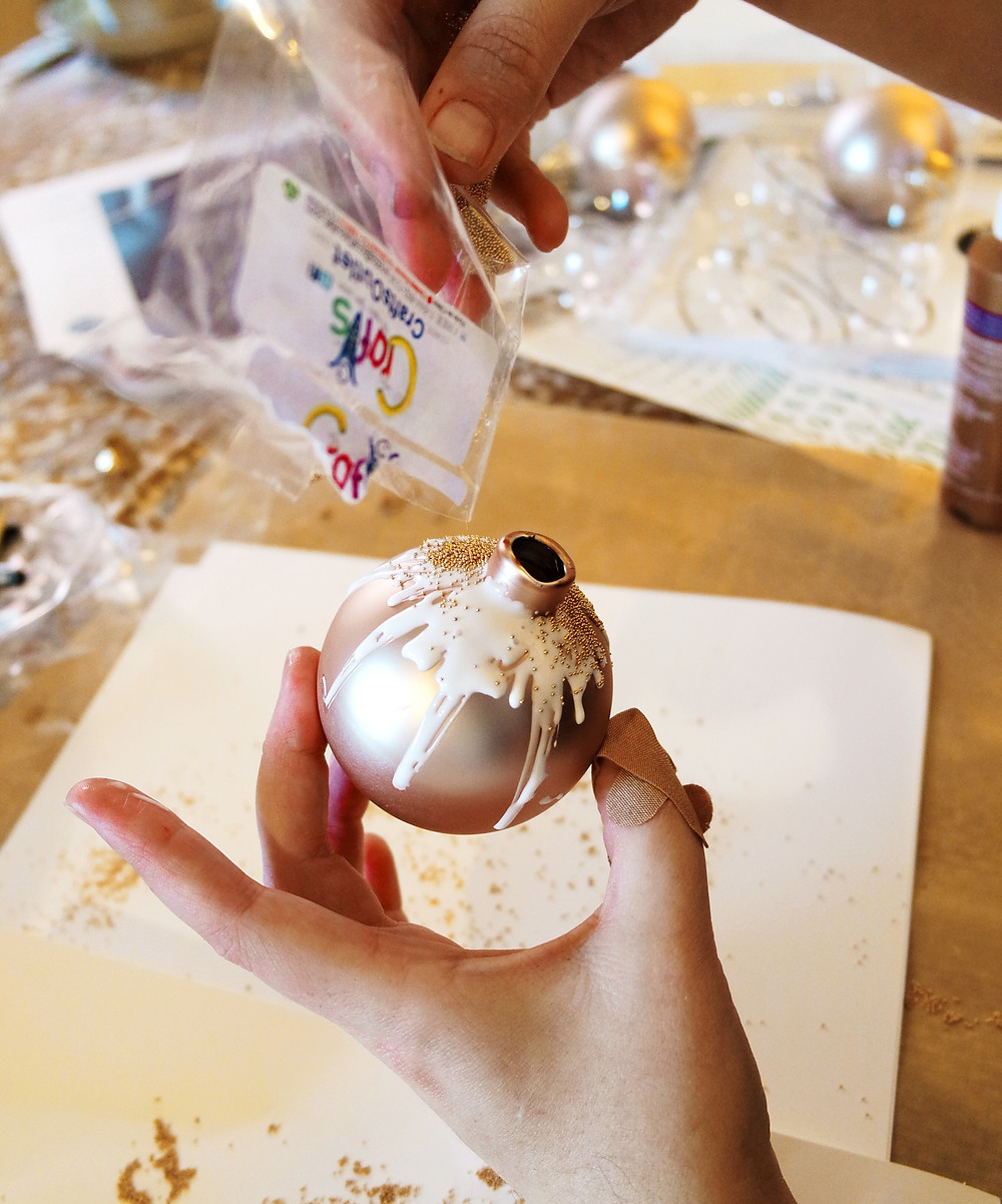 Hand pouring gold micro beads onto the ornament from a clear plastic bag.