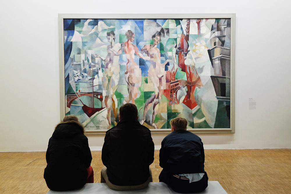 Three men sitting in front of a large cubist painting showing three nude women standing in front of a city.