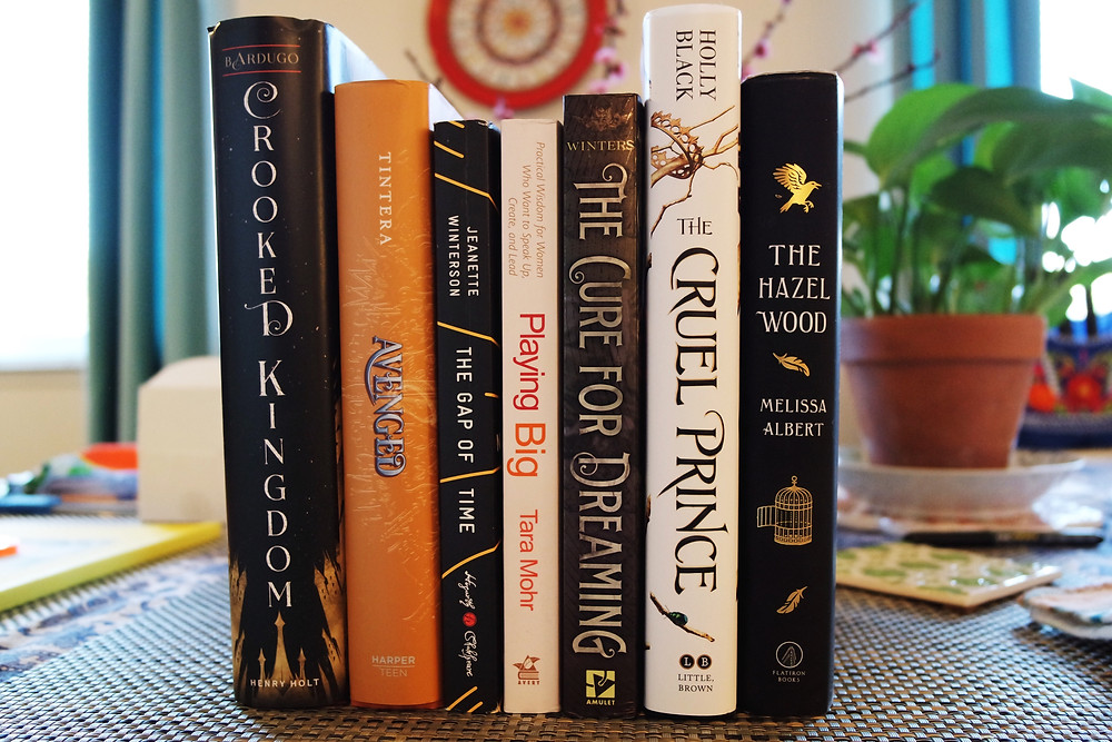 Books on a table - Crooked Kingdom, Avenged, The Gap of Time, Playing Big, The Cure for Dreaming, The Cruel Prince, and The Hazel Wood