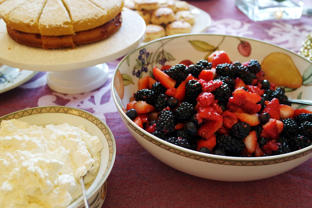 Large bowl of mixed berries on a purple and white tablecloth next to a smaller bowl of whippe cream.