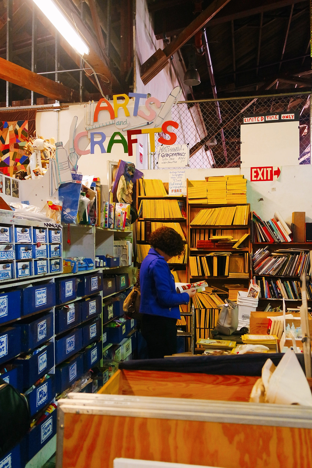 Woman with red curly hair looking at a magazine in the Arts and Crafts area of SCRAP.