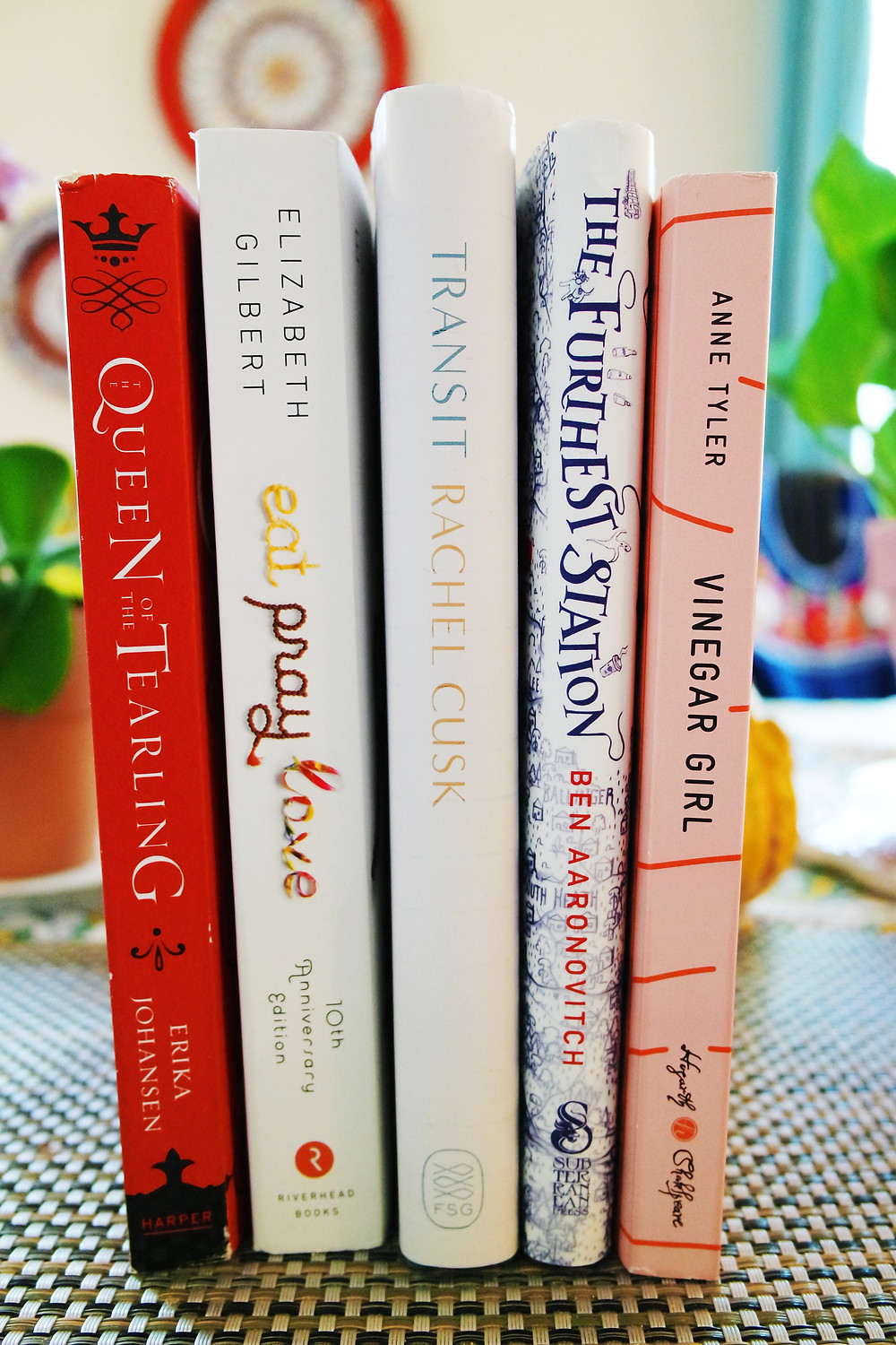 Five books standing on a table - Queen of the Tearling, Eat Pray Love, Transit, The Furthest Station, and Vinegar Girl,