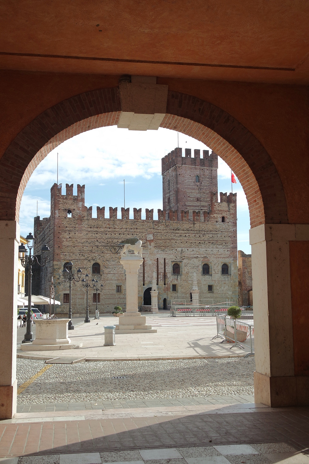 A brick arch looking out onto the square of Marostica and the medieval stone gate house with tower and crenelations.