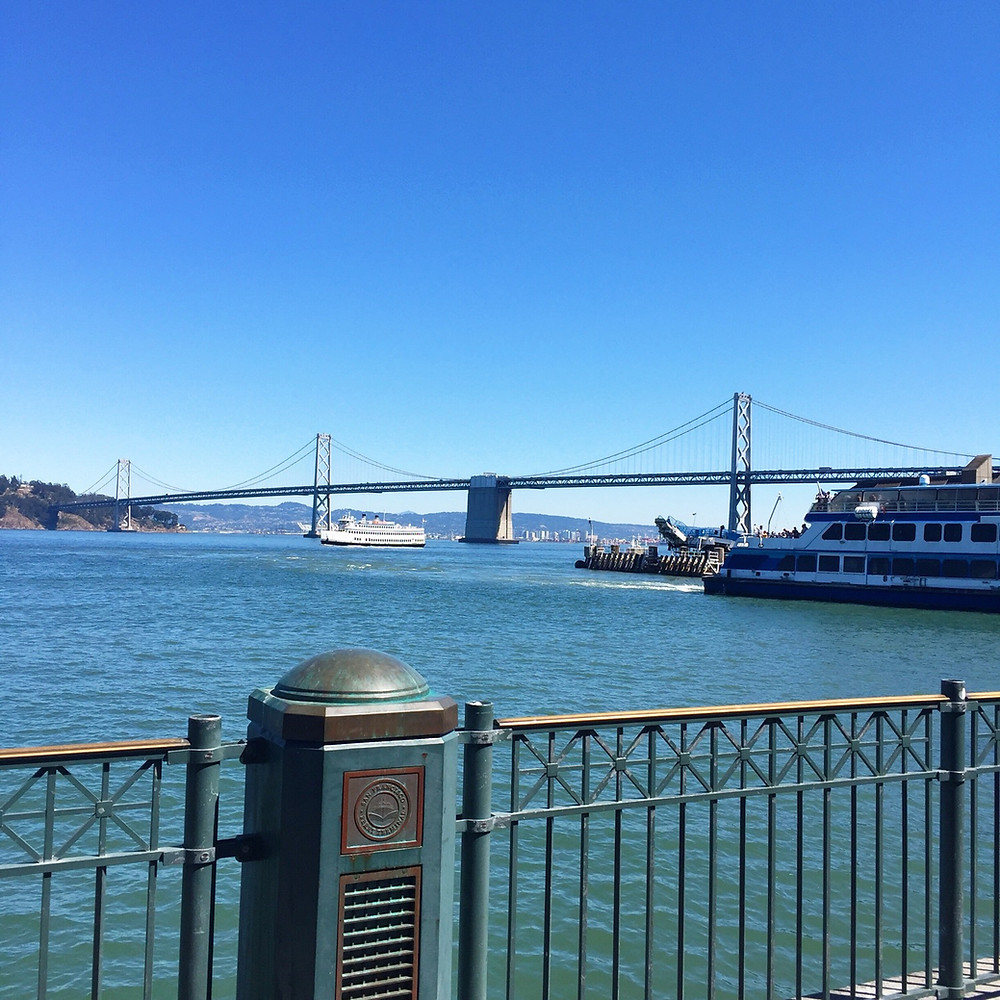 A shot of the Bay Bridge from the San Francisco Ferry Building looking across the water towards Oakland. A ferry sails out from under the bridge.