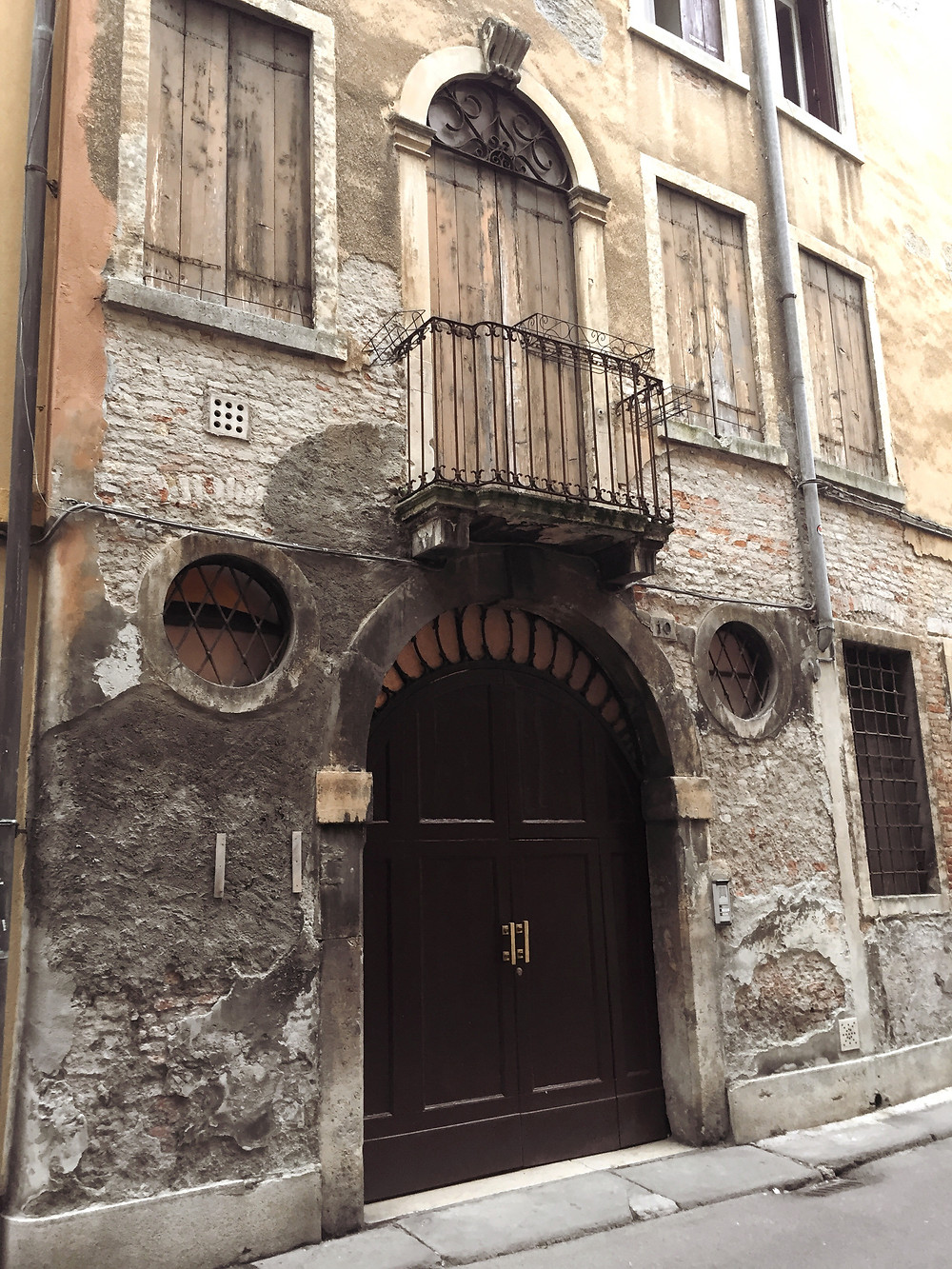 The stone facade of an old building in Vicenza, with a large wooden door, a smaller wooden door leading to a balcony with an iron railing directly above, and rectangular windows with wooden shutters.