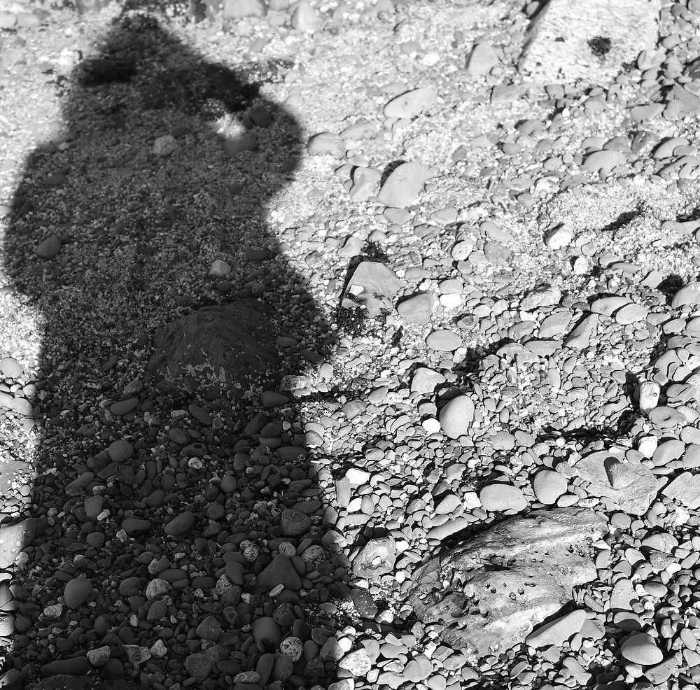 Black and white photo of Sophia's shadow, holding a camera, against a bed of rocks.