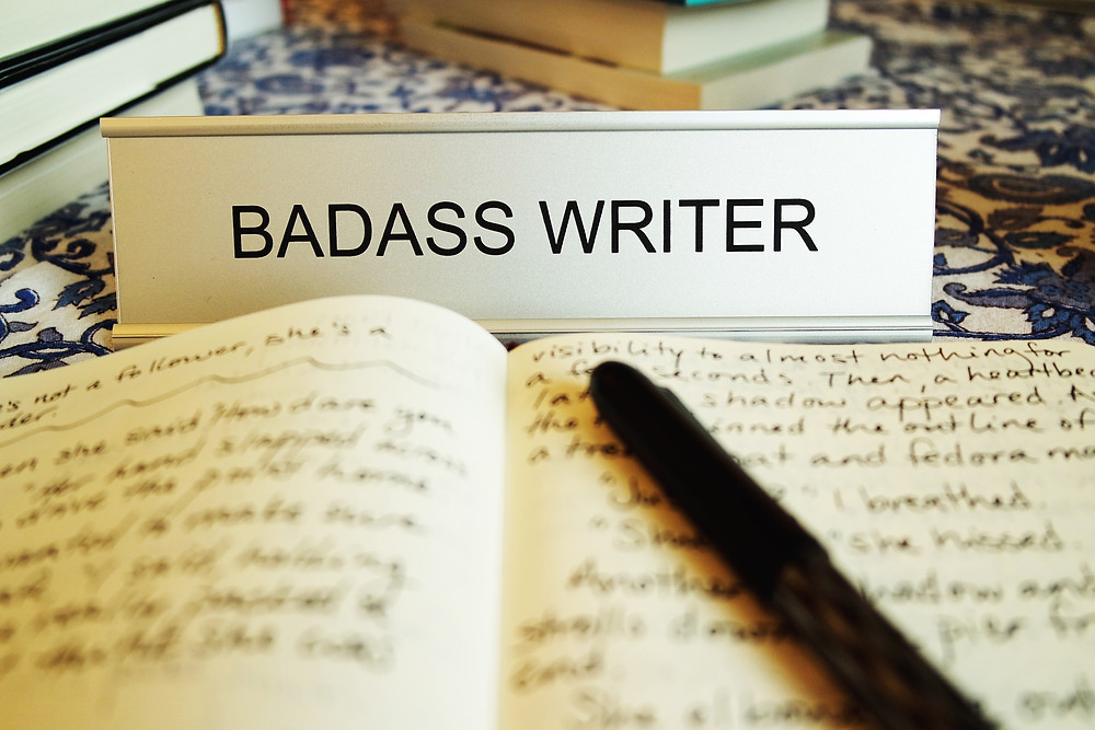 Name plate reading - Badass Writer, in front of an open notebook and pen.