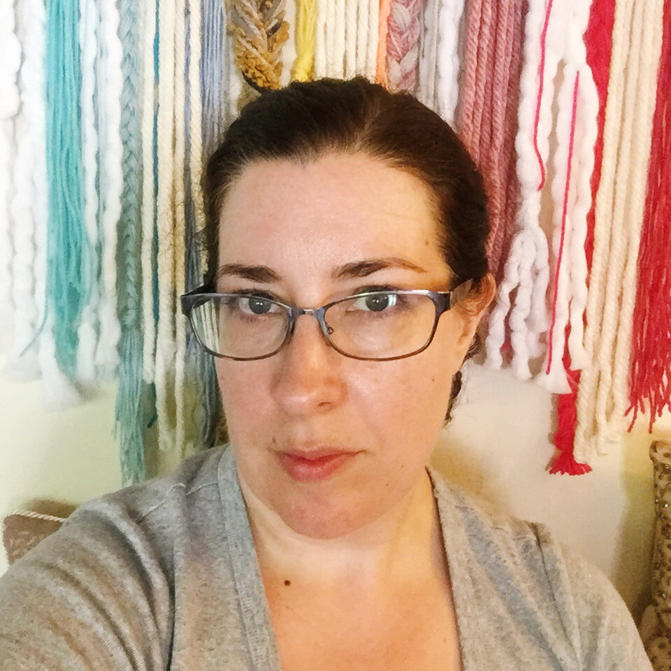 A selfie headshot of Sophia Dunkin-Hubby standing in front of a yarn wall hanging in rainbow colors.