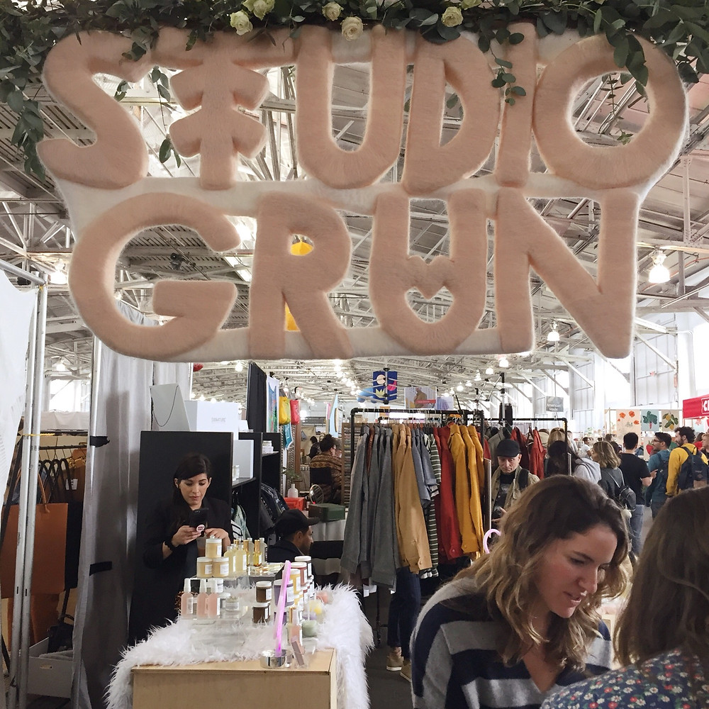 "A sign made out of pink wool that says ""Studio Grun"" hanging above a booth at the Renegade Craft Fair in San Francisco."