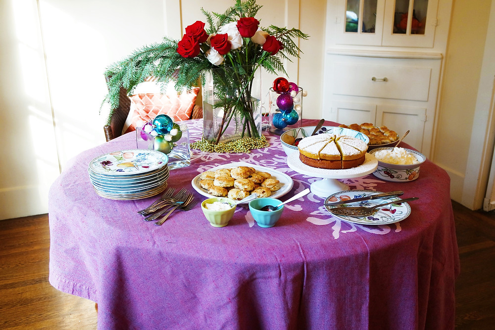 Round table in a brightly lit dining room with a purple table cloth, a stack of floral plates, a platter of scones with small bowls of clotted cream and jam, a white cake stand with a victoria sponge cake, a large bowl of berries, a bowl of whipped cream, and a plate of cornish pasties. in the center of the table are two vases with colored glass ornaments, and a vase with red and white roses and evergreen branches.