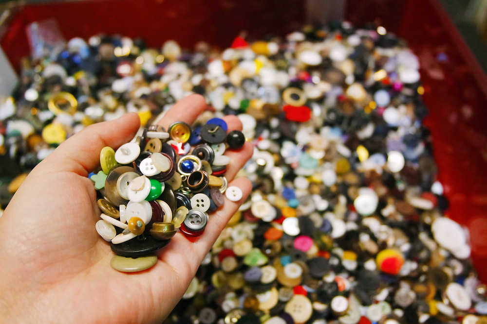 A hand holding a small pile of buttons over a large bin of buttons.