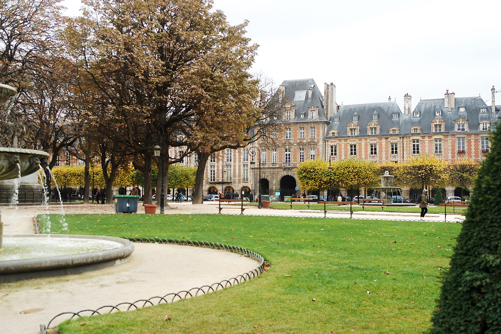 View of one side of the buildings of the Place des Vosges, with its red brick facade, from the central square with green grass and the edge of the fountain just in view on the left.