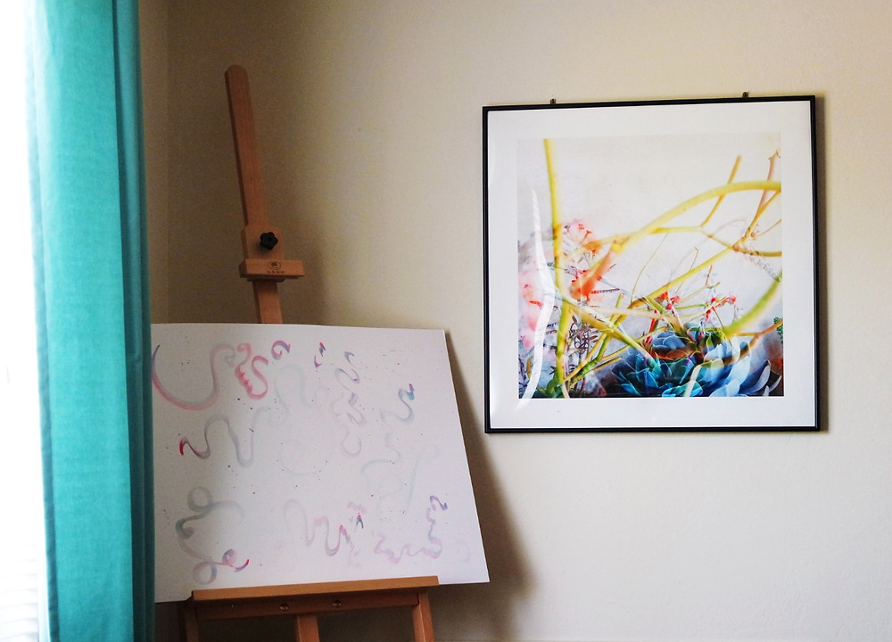 Framed photograph of a double exposure shot of colorful plants from South Africa, handing on a wall next to an easel with a pad of paper and a in progress watercolor painting of pastel squiggles.