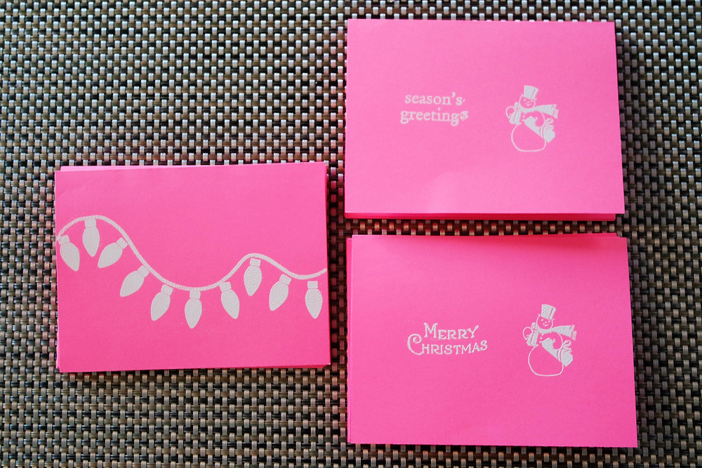 """Three sets of hot pink and white Christmas cards - one with a string of Christmas lights, one with a snow man and the phrase """"season's greetings"""", and one with a snow man and the phrase """"Merry Christmas""""."""