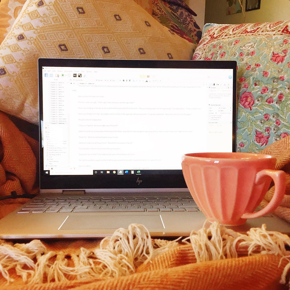 Open laptop sitting on top of a blanket on a couch with a coral mug sitting on one side. There are pillows behind it.