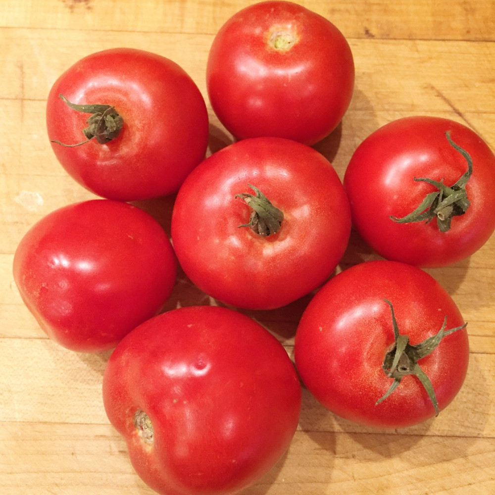 Seven tomatoes on a wooden cutting board.