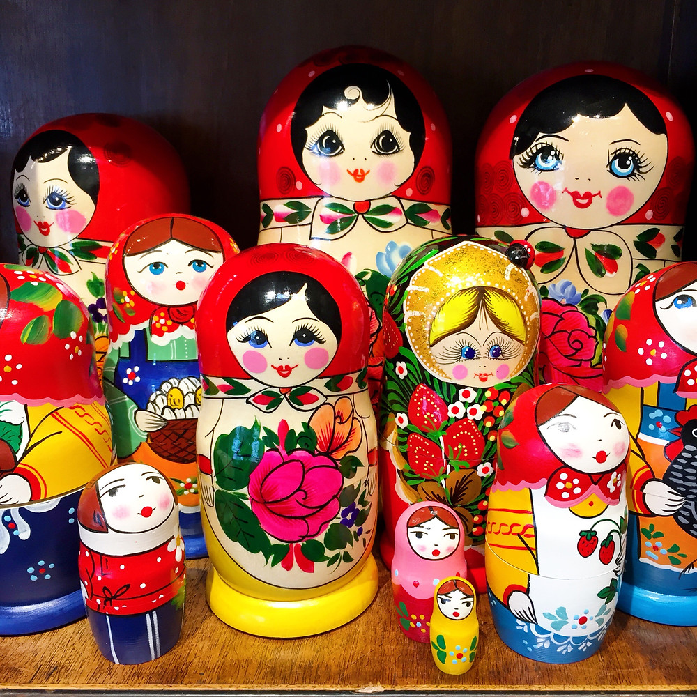 A display of Russian nesting dolls of all sizes, with different color dresses and faces, displayed on a shelf.