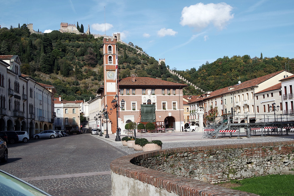 View of Marostica's main square, in front of a hill with a castle on top and wall lining its curves.