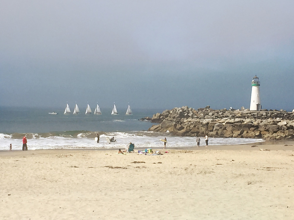 Sandy beach with a rocky pier and lighthouse on the right and sailboats out on the water