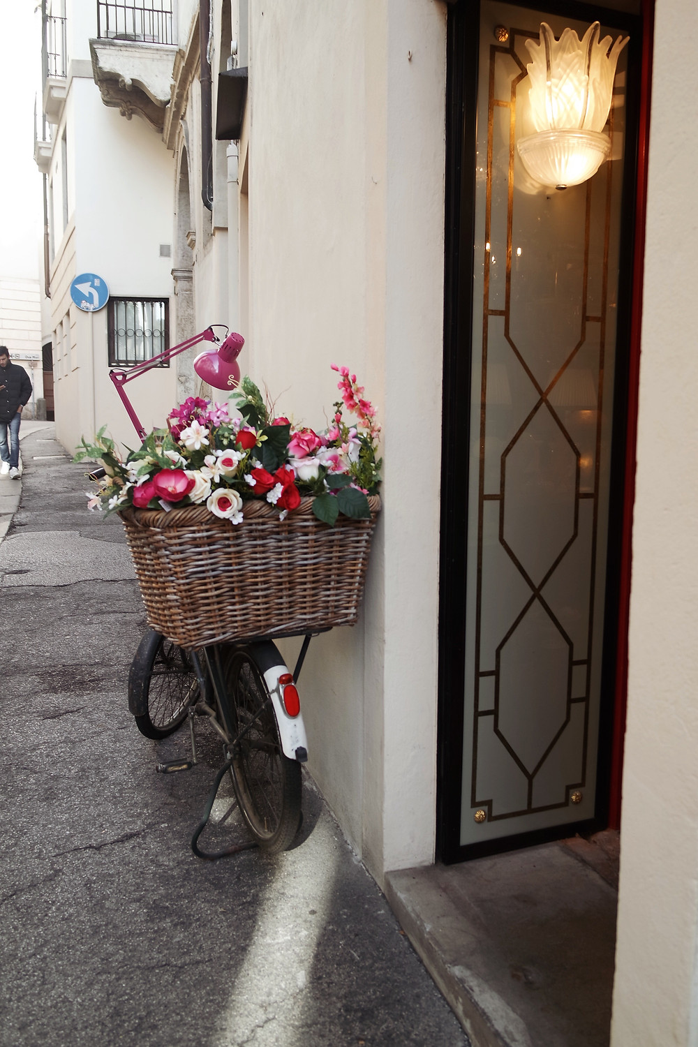 Bicycle parked next to a white building with a basket full of flowers.