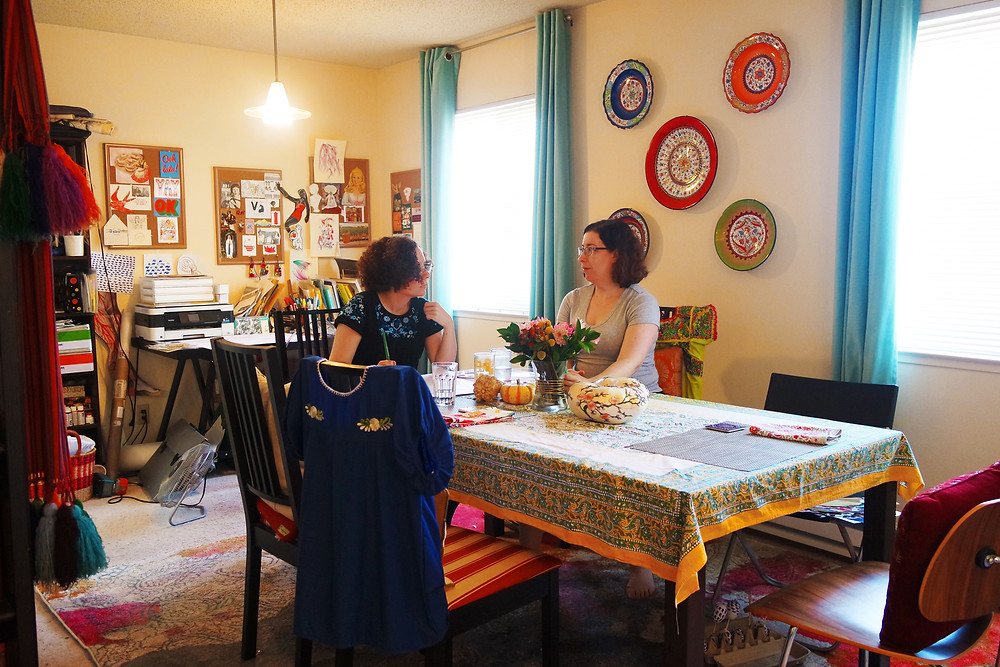 Shot of two women sitting in a dining room with light blue curtain, with a desk/art studio on the far wall.