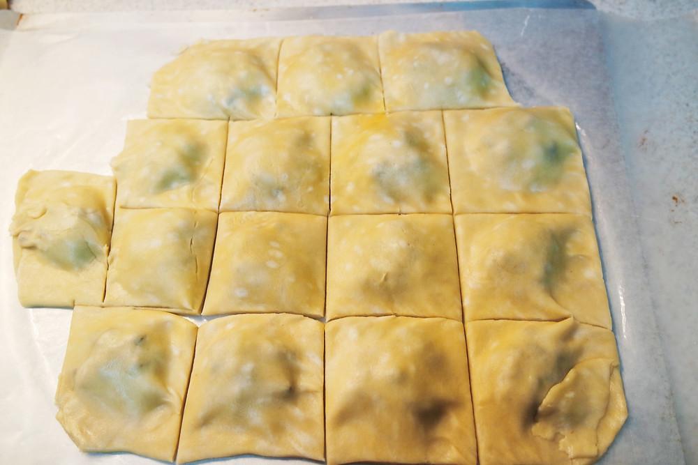 Unbaked pie crust dough cut into squares.