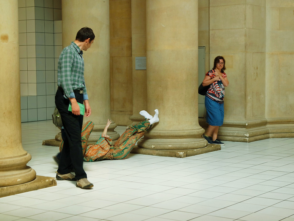 Two people walking through a museum hall with white tile floor and large columns, looking a a performance artist dressed in red and green marbled fabric and white socks, wearing a oddly shaped mask/helmet that completely covers their head, lying on the floor.