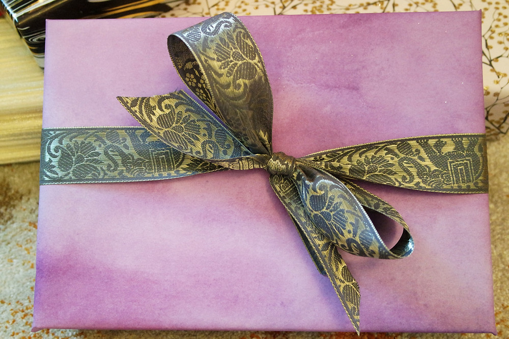 Purple water color wrapping paper with silver figured ribbon.
