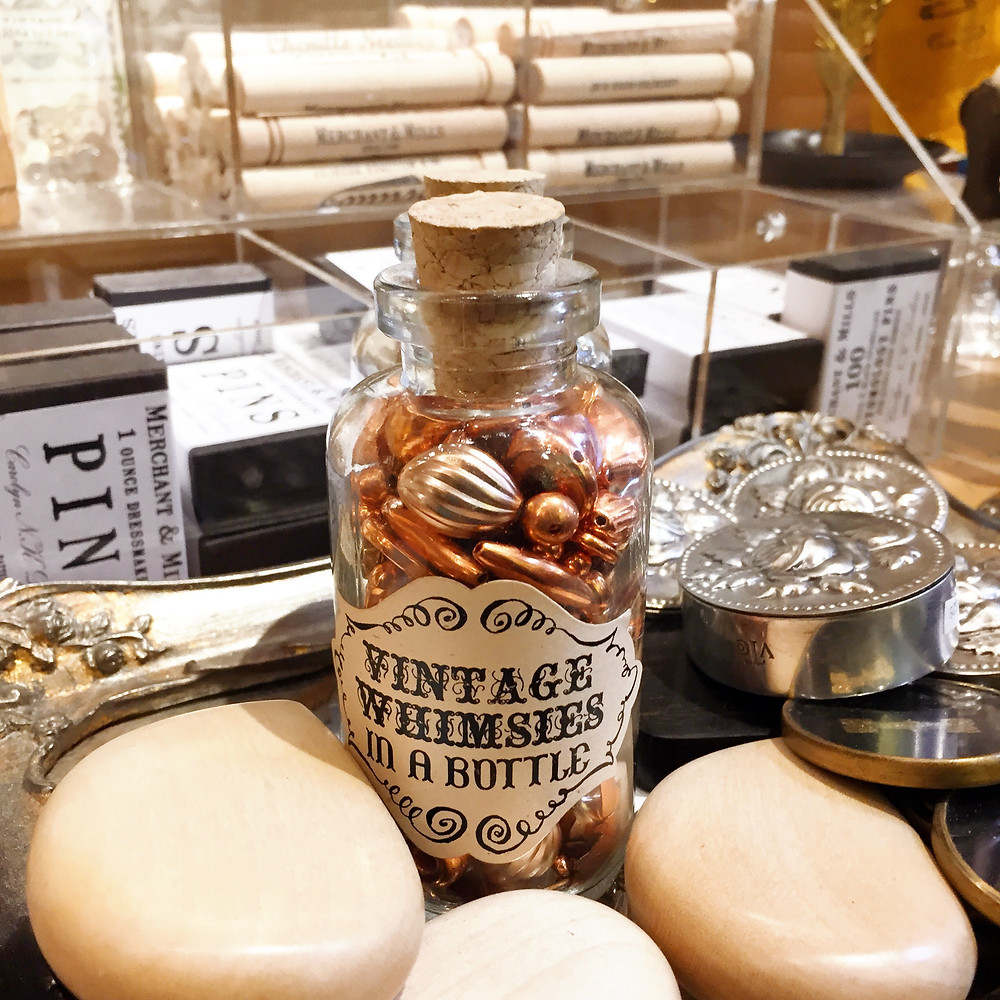 A bottle filled with copper colored beads of various sizes labelled - Vintage Whimsies in a bottle - with a cork stopper, surrounded by vintage boxes of pins, silver round tins, and wooden hearts.