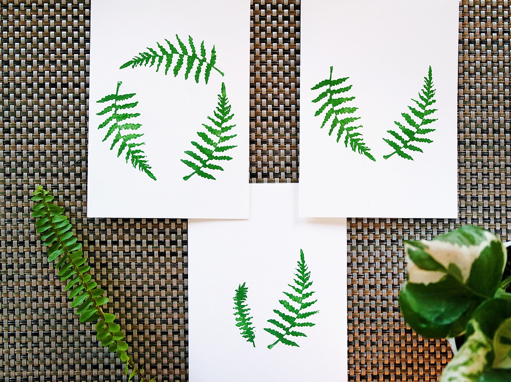 Three white cards on a gray textured place mat. Each one has a different design stamped on it with green fern leaves - 3 stamps in a circle, 2 stamps in an open, curved, V, a larger fern and a smaller fern leaf in a closer V. A real fern leaf sits in the lower left corner.
