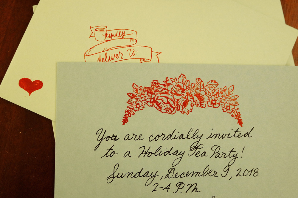 "Green Flat cards with a red floral stamp on the top and the words ""You are cordially invited to a holiday Tea Party! Sunday, December 9, 2018, 2-4 PM""."