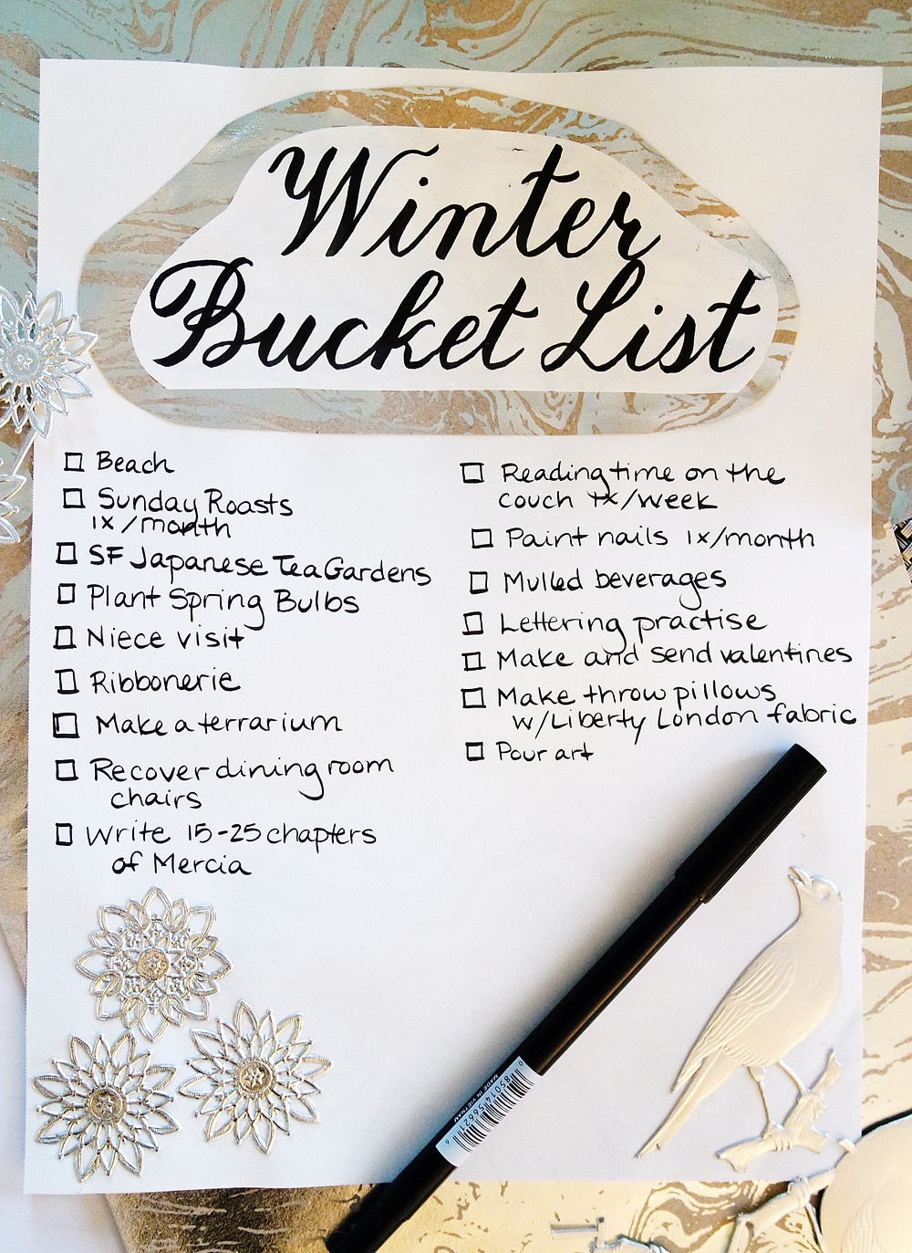 Winter Bucket List - title in black fancy lettering pasted over silver and brown paper and in the bottom three silver star on the left and on the right a silver bird.