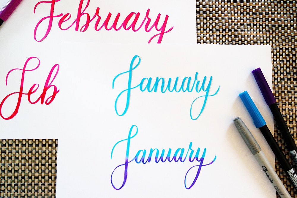 Two sheets of white paper lying on a textured mat. The top one has January in script written on it twice in blue, with the bottom one written in blue and purple. The other paper has February written twice in red and pink.