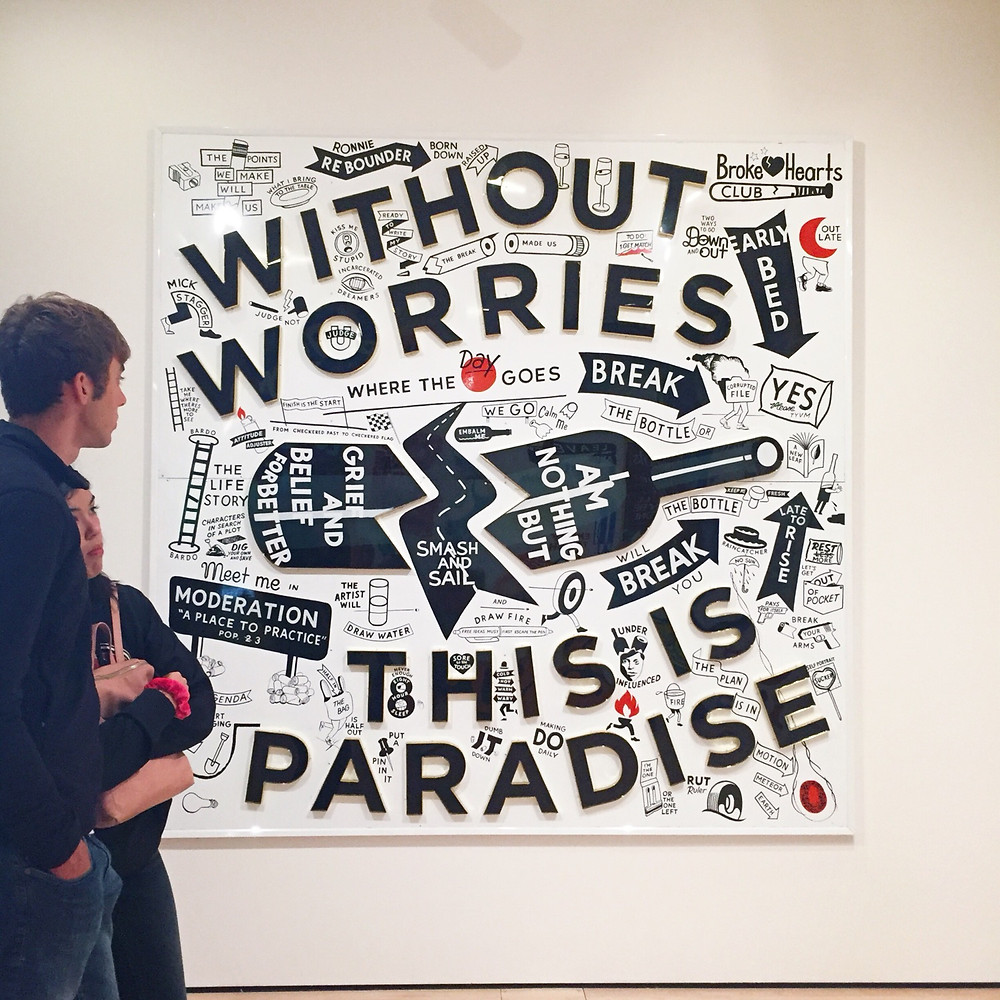 A framed mural with black text and images on a white background. The main text says Without worries this is paradise.