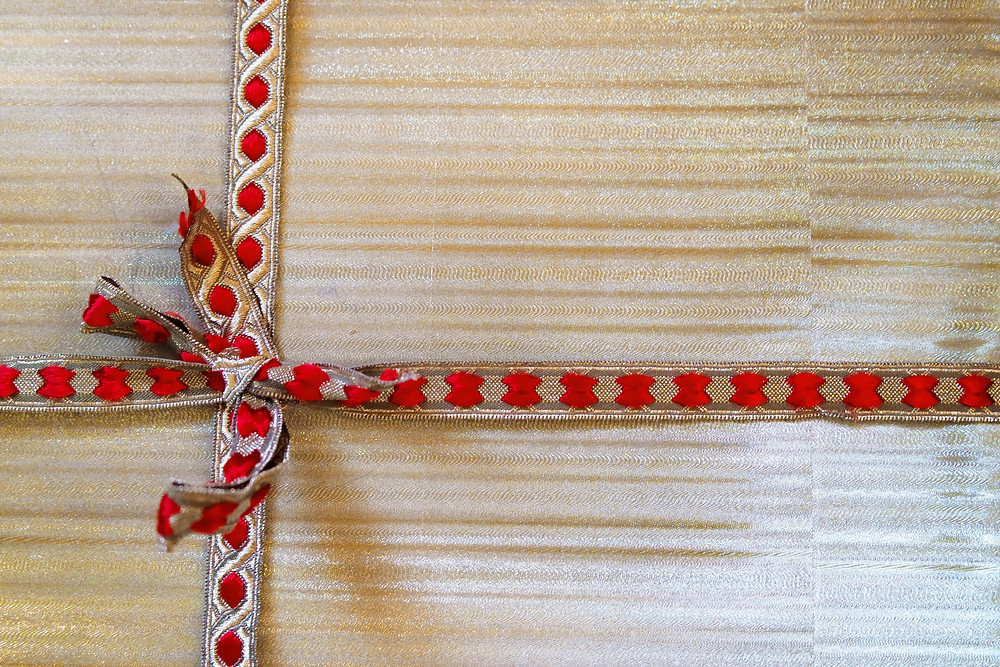 Gold wrapping paper with gold and red ribbon.