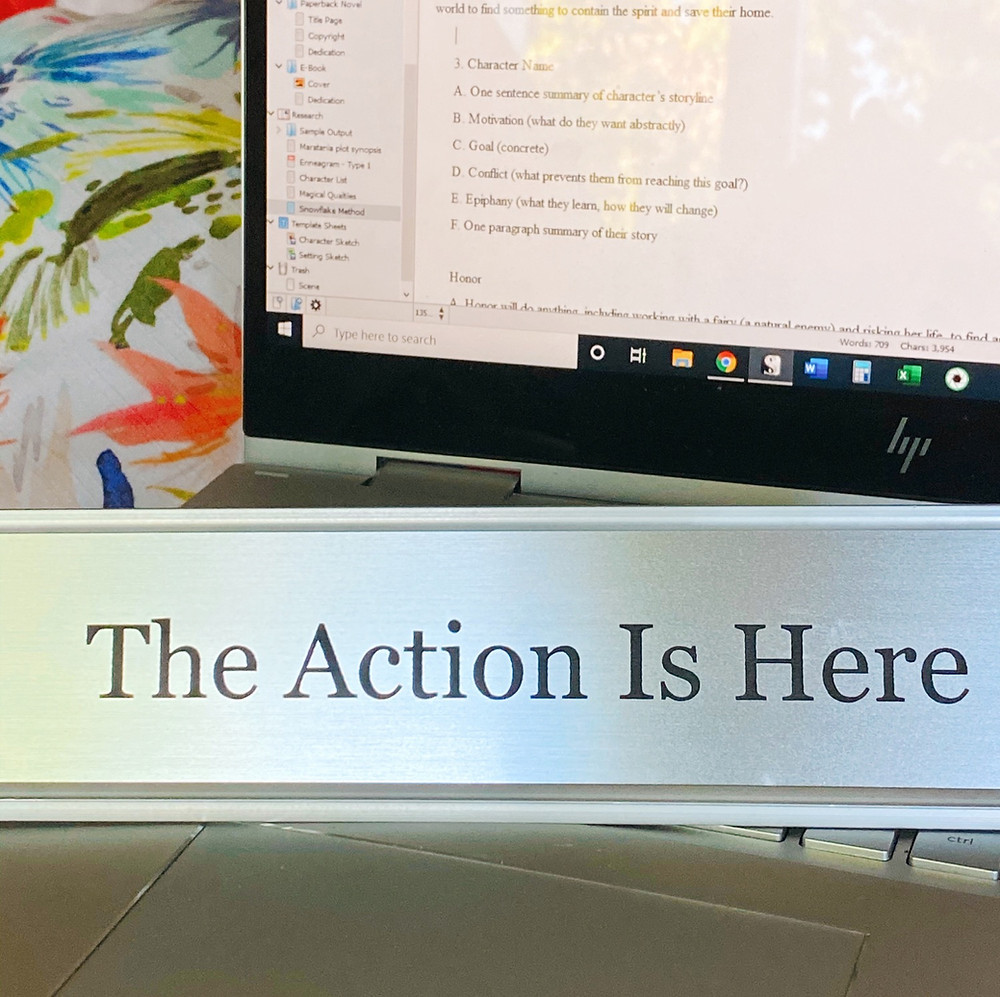 """A silver, metal name plate holder with a silver name plate that says """"The Action Is Here"""" sitting on a laptop keyboard with the screen showing step 3 of the snowflake method and a floral watercolor pillow in the background."""