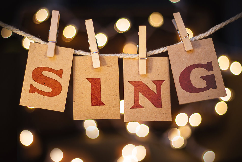 The word SING printed on clothespin clipped cards in front of defocused glowing lights..jpg