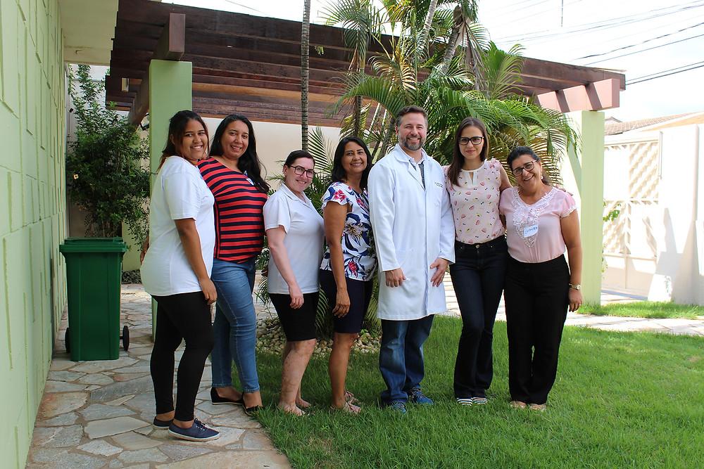 Foto da equipe céu de Brigadeiro, com o consultor médico ao centro, na entrada da escola, com grama, pedras e plantas de cenário